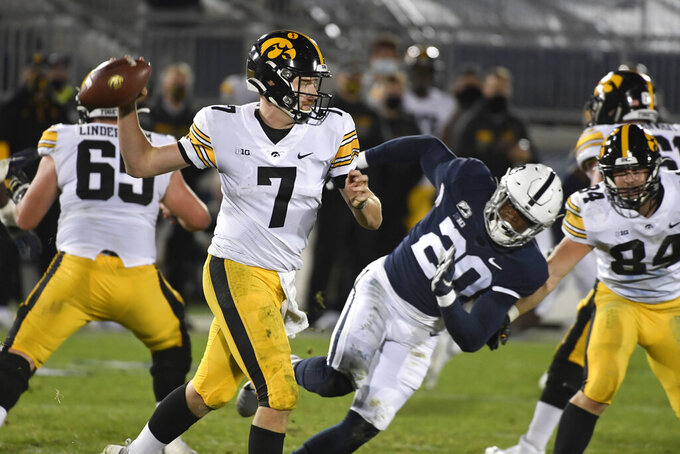 Iowa quarterback Spencer Petras (7) looks to pass as Penn State defensive end Adisa Isaac (20) rushes him during the fourth quarter of an NCAA college football game in State College, Pa., on Saturday, Nov. 21, 2020.Iowa defeated Penn State 41-21. (AP Photo/Barry Reeger)