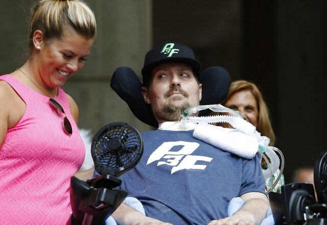 FILE - In this Sept. 5, 2017, file photo, Pete Frates, right, who inspired the ice bucket challenge, looks at his wife Julie during a ceremony at City Hall in Boston by Boston Mayor Marty Walsh declaring the day the Pete Frates Day. Frates, who was stricken with amyotrophic lateral sclerosis, or ALS, died Monday, Dec. 9, 2019. He was 34. (AP Photo/Bill Sikes, File)