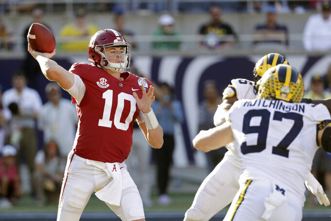 Alabama quarterback Mac Jones (10) throws a pass as Michigan defensive lineman Aidan Hutchinson (97) rushes during the second half of the Citrus Bowl NCAA college football game, Wednesday, Jan. 1, 2020, in Orlando, Fla. (AP Photo/John Raoux)