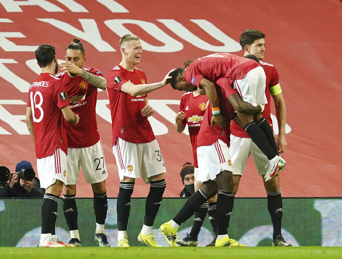 Manchester United players celebrate after Manchester United's Amad Diallo scored his side's opening goal during the Europa League round of 16 first leg soccer match between Manchester United and AC Milan at Old Trafford in Manchester, England, Thursday, March 11, 2021. (AP Photo/Dave Thompson)