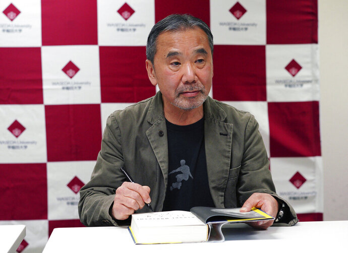 FILE - In this Nov. 3, 2018, file photo, Japanese novelist Haruki Murakami signs his autograph on his novel