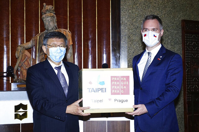 In this photo released by the Taipei City Government, Taipei's Mayor Ko Wen-je, left, hands over a box of surgical masks to Prague's Mayor Zdenek Hrib during a meeting in Taipei, Taiwan on Friday, Sept. 4, 2020. The mayors of Prague and Taipei announced new areas of cooperation for the two sister cities, including orchestra tours, on Friday as a Czech delegation concluded a weeklong visit to Taiwan that was bitterly criticized by China. (Taipei City Government via AP)