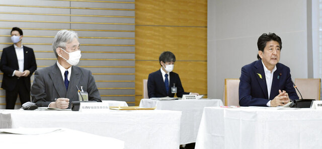 Japanese Prime Minister Shinzo Abe, right, attends a government meeting on space development at his office in Tokyo Monday, June 29, 2020. Japan said Monday it will step up its defense capability in space and improve its ability to detect and track missiles, while cooperating with the United States in response to what it called a growing threat from North Korea and China.  (Kyodo News via AP)
