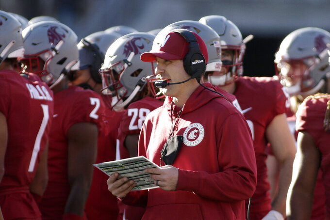 Washington State defensive coordinator and linebackers coach Jake Dickert, center, stands on the field during a break in play in the second half of an NCAA college football game, Saturday, Oct. 9, 2021, in Pullman, Wash. Dickert was named Washington State interim head coach, Monday, Oct. 18 after head coach Nick Rolovich was fired for refusing a state mandate that all employees get vaccinated against COVID-19. (AP Photo/Young Kwak)