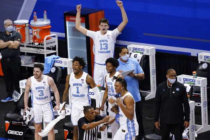 The North Carolina bench celebrates a play during the second half of an NCAA college basketball game against Notre Dame in the second round of the Atlantic Coast Conference tournament in Greensboro, N.C., Wednesday, March 10, 2021. UNC won the game 101-59. (AP Photo/Gerry Broome)