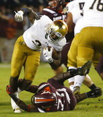 Notre Dame running back Dexter Williams (2) tries to gain yardage as Virginia Tech defensive back Reggie Floyd (21) makes the stop during the second half of an NCAA college football game in Blacksburg, Va., Saturday, Oct. 6, 2018. Notre Dame won 45-23. (AP Photo/Steve Helber)