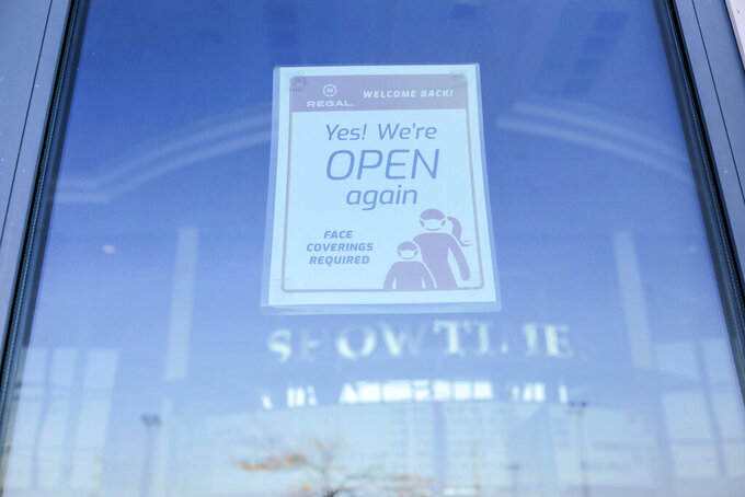 A sign is posted on a window of Regal Edwards Grand Teton theater in Idaho Falls, Idaho on Monday, Oct. 5, 2020. Cineworld, which owns Regal, Cineworld and Picturehouse movie theaters, will suspend operations after the release of the latest James Bond film was postponed again, deflating hopes that a blockbuster could revive the devastated industry.(John Roark/The Idaho Post-Register via AP)