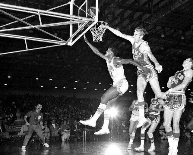 FILE - In this Nov. 28, 1968, file photo, Miami Floridians' Les Hunter (41) is fouled by Oakland Oaks' Jim Eakins (42) while scoring a basket during an ABA basketball game in Miami. Hunter, a star on Loyola Chicago's barrier-breaking 1963 NCAA championship team, died Friday, March 27, 2020, the school said. He was 77 and had been battling cancer. (AP Photo/Toby Massey, File)