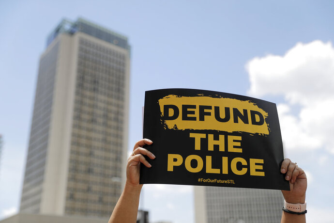 A person holds up a sign advocating for defunding the police as people gather to mark Juneteenth, Friday, June 19, 2020, in St. Louis. Juneteenth is the holiday celebrating the day in 1865 that enslaved black people in Galveston, Texas, learned they had been freed, more than two years after the Emancipation Proclamation was signed. (AP Photo/Jeff Roberson)