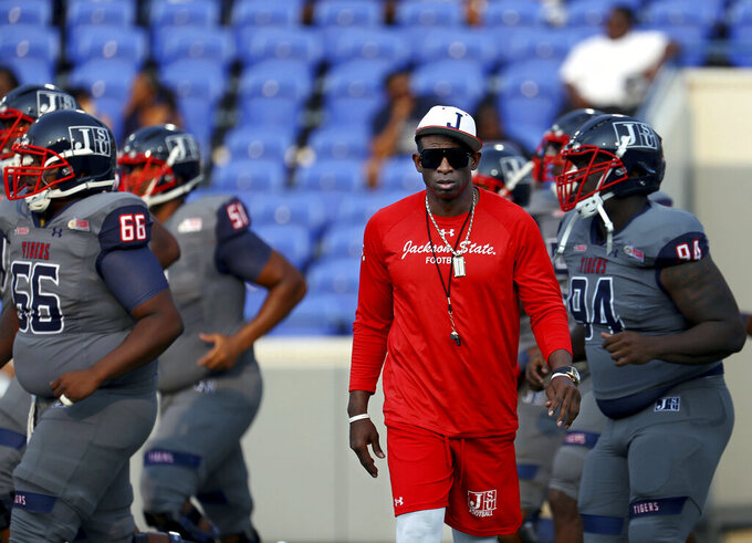 Jackson State head coach Deion Sanders works with his players before the Southern Heritage Classic NCAA college football game against Tennessee State in Memphis, Tenn., Saturday, Sept. 11, 2021. (Patrick Lantrip/Daily Memphian via AP)