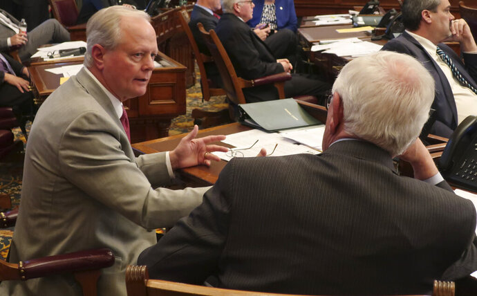 Kansas state Sen. Gene Suellentrop, left, R-Wichita, confers with Sen. Rick Wilborn, right, R-McPherson, during a debate on a tax relief bill, Wednesday, Feb. 6, 2019, at the Statehouse in Topeka, Kansas. Republicans are pushing the measure to prevent individuals and businesses from paying higher income taxes to the state because of federal tax changes. (AP Photo/John Hanna)