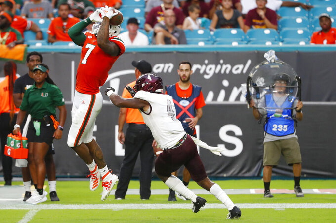 Miami wide receiver Brian Hightower (7) catches a pass as he is guarded by Bethune-Cookman cornerback De'Ron Maxwell (4) during the second half of an NCAA college football game, Saturday, Sept. 14, 2019, in Miami Gardens, Fla. (AP Photo/Wilfredo Lee)