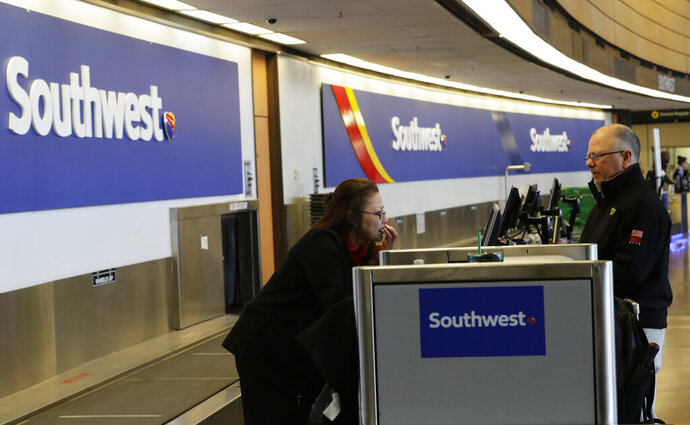 FILE - In this March 13, 2019, file photo a traveler checks in with Southwest Airlines at Seattle-Tacoma International Airport in Seattle. Southwest Airlines Co. reports earns on Thursday, April 25. (AP Photo/Ted S. Warren, File)