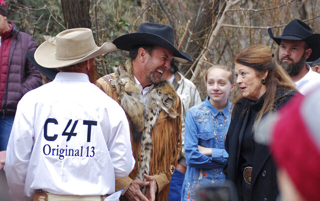 FILE - In this March 12, 2019, file photo, Cowboys for Trump leader and Otero County Commissioner Couy Griffin, center, talks with Republican New Mexico state Rep. Candy Ezzell of Roswell, N.M., at a protest against gun control and pro-abortion rights legislation outside the New Mexico state Capitol, in Santa Fe, N.M. The Mescalero Apache Tribe of New Mexico announced Monday, Sept. 28, 2020, that Griffin has been banned from tribal lands after posting a video of himself on the reservation laughing during a traditional Apache ceremony and referencing Democratic House Speaker Nancy Pelosi. (AP Photo/Morgan Lee,File)