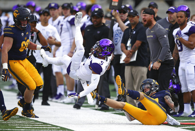 Washington's Andre Baccellia (5) is upended by California's Ashtyn Davis, right, during the first half of an NCAA college football game Saturday, Oct. 27, 2018, in Berkeley, Calif. (AP Photo/Ben Margot)