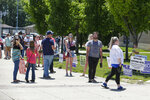 Voters wait in a line outside Perry Meridian High school to vote in the Indiana primary in Indianapolis, Tuesday, June 2, 2020 after coronavirus concerns prompted officials to delay the primary from its original May 5 date. Voters waited up to two hours to cast their ballots. Nearly 550,000 voters requested mail-in ballots, more than 10 times the number of those ballots cast during the 2016 primary. (AP Photo/Michael Conroy)