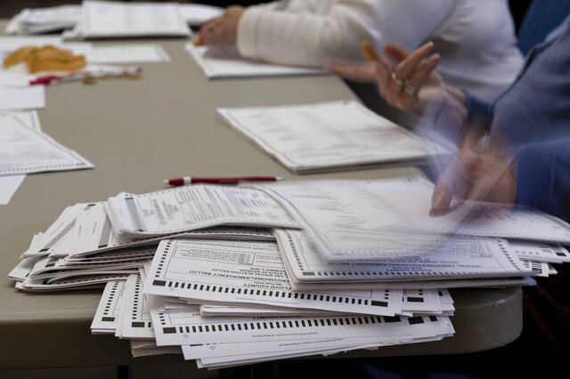 FILE - In this Nov. 13, 2020, file photo officials sort ballots during an audit at the Floyd County administration building in Rome, Ga. (AP Photo/Ben Gray, File)