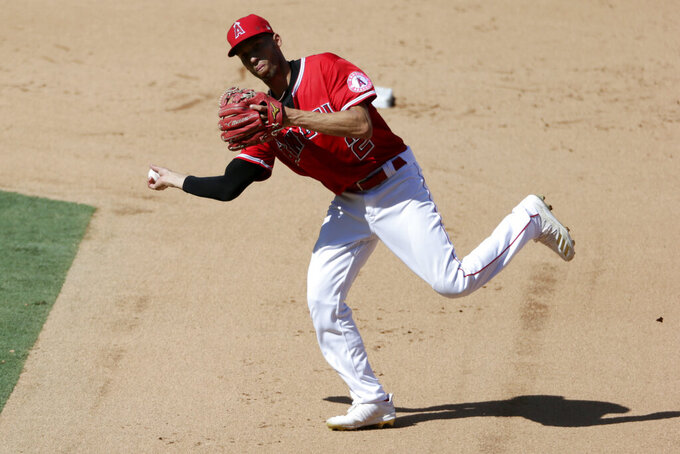 FILE - Then-Los Angeles Angels shortstop Andrelton Simmons throws to first to get Texas Rangers' Rougned Odor out on a ground ball during the sixth inning of a baseball game in Anaheim, Calif., in this Sunday, Sept. 20, 2020, file photo.  After a travel documentation delay in his native country Curaçao, new shortstop Andrelton Simmons has finally settled in at spring training with the Minnesota Twins, who are getting a big boost to the left side of their infield from the 31-year-old glove whiz. (AP Photo/Alex Gallardo, File)
