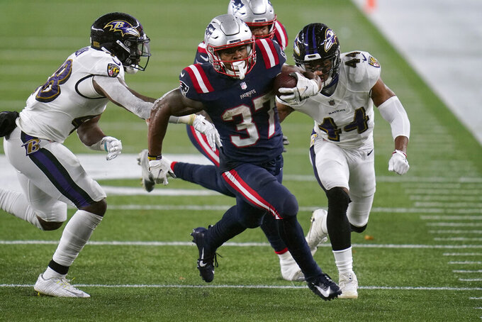 New England Patriots running back Damien Harris, center, runs past Baltimore Ravens linebacker Patrick Queen, left, and cornerback Marlon Humphrey, right, in the first half of an NFL football game, Sunday, Nov. 15, 2020, in Foxborough, Mass. (AP Photo/Charles Krupa)