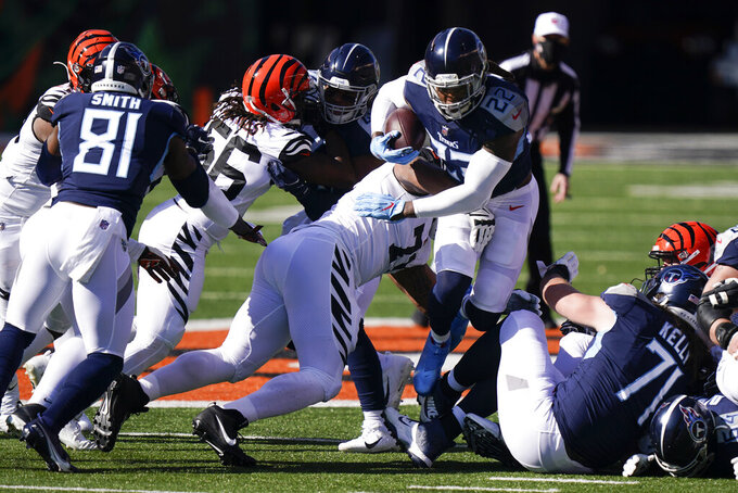 Tennessee Titans' Derrick Henry (22) is tackled by Cincinnati Bengals' Xavier Williams (71) during the first half of an NFL football game, Sunday, Nov. 1, 2020, in Cincinnati. (AP Photo/Bryan Woolston)