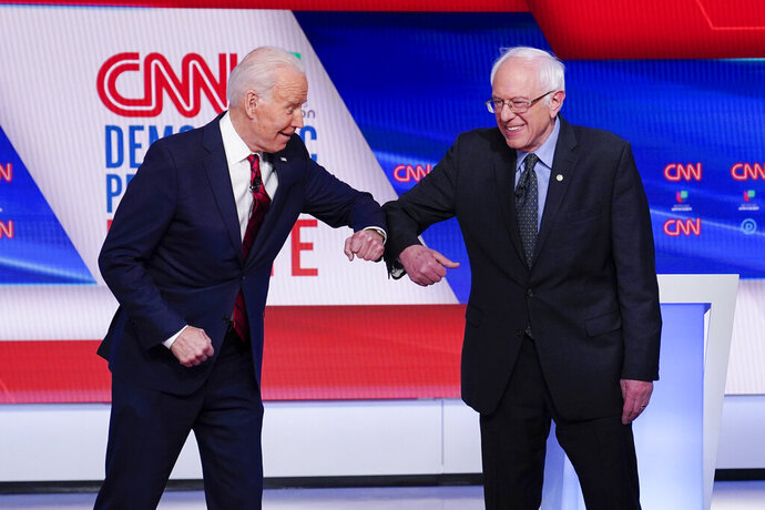 FILE - In this March 15, 2020 file photo, now Democratic presidential candidate former Vice President Joe Biden, left, and Sen. Bernie Sanders, I-Vt., right, greet one another before they participate in a Democratic presidential primary debate at CNN Studios in Washington. Former staffers from Bernie Sanders' presidential campaign want to harness strong support for the Vermont senator among Hispanics to bolster Joe Biden in two battleground states that could prove critical in November's election. Nuestro PAC is launching a 30-second spot that will begin airing Thursday for two weeks in heavily Hispanic Nevada and Iowa. (AP Photo/Evan Vucci)