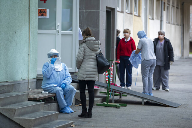 A health worker takes notes at the infectious disease clinic in Zagreb, Croatia, where the first coronavirus case in Croatia is hospitalized, Tuesday, Feb. 25, 2020. Croatia confirmed its first case of coronavirus in a man who had been to Milan, the capital of Lombardy, Italy. (AP Photo/Darko Bandic)