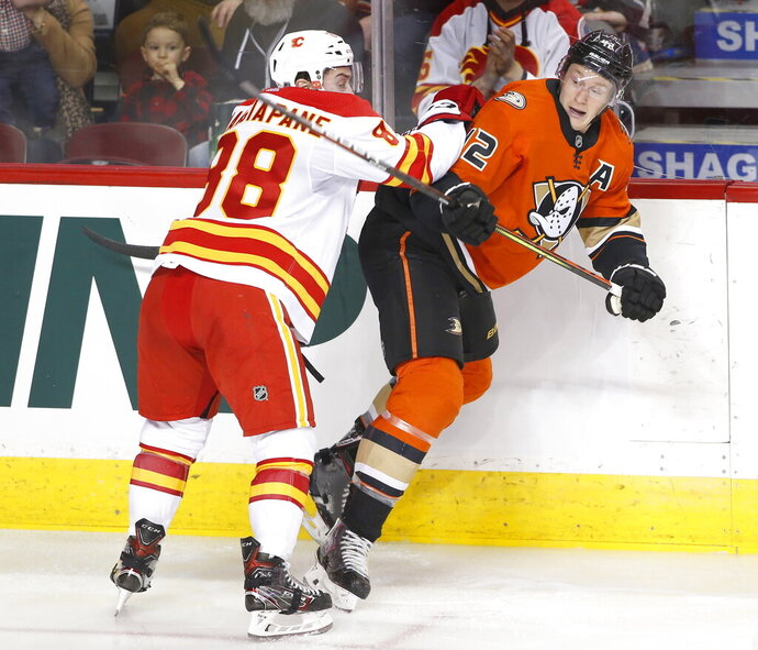 Anaheim Ducks' Josh Manson, right, takes a hit from Calgary Flames' Andrew Mangiapane during second period NHL hockey action in Calgary, Alberta, Monday, Feb. 17, 2020. (Larry MacDougal/The Canadian Press via AP)