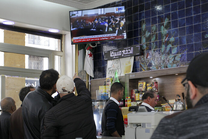 People watch the trial of former Algerian Prime Ministers Ahmed Ouyahia and Abdelmalek Sellal, in a cafe of Algiers, Wednesday, Dec.4, 2019. Ahmed Ouyahia, who was forced out as prime minister in March as protests against President Abdelaziz Bouteflika escalated, and his predecessor Abdelmalek Sellal, are facing questions Wednesday and face corruption charges. (AP Photo/Toufik Doudou)