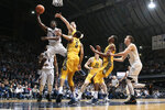 Butler guard Kamar Baldwin (3) shoots between Marquette defenders Sam Hauser and Greg Elliott (5) during the first half of an NCAA college basketball game in Indianapolis, Friday, Jan. 12, 2018. (AP Photo/AJ Mast)