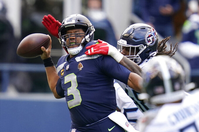 Seattle Seahawks quarterback Russell Wilson is pressured by Tennessee Titans outside linebacker Bud Dupree, right, late in the fourth quarter of an NFL football game against the Tennessee Titans, Sunday, Sept. 19, 2021, in Seattle. The Titans won 33-30 in overtime. (AP Photo/Elaine Thompson)