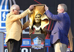 Former NFL player Johnny Robinson, left, unveils his bust with presenter Bob Thompson during the induction ceremony at the Pro Football Hall of Fame, Saturday, Aug. 3, 2019, in Canton, Ohio. (AP Photo/David Richard)