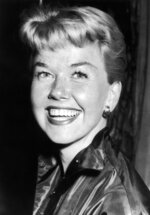 FILE - In this April 12, 1955 file photo, film actress and singer Doris Day smiles in London. Day, whose wholesome screen presence stood for a time of innocence in '60s films, has died, her foundation says. She was 97. The Doris Day Animal Foundation confirmed Day died early Monday, May 13, 2019, at her Carmel Valley, California, home. (AP Photo/Bob Dear, File)