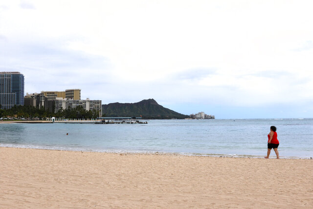 In this April 21, 2020, photo, a woman walks on Waikiki Beach in Honolulu. Hawaii has some of the lowest coronavirus infection and mortality rates in the U.S. As cases started to rise in March, the governor did something no other state can — effectively seal the borders. People who do come face a two-week quarantine. That's cut off the flow of tens of thousands of tourists a day. But it's walloped an economy that relies on tourism, and officials say travel restrictions will be among the last to end. Of the few remaining places in the world with no confirmed infections, nearly all are islands in the Pacific. American Samoa, a U.S. territory west of Hawaii, is the nation's only jurisdiction with no cases to date. (AP Photo/Caleb Jones)