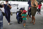 Enrique Calvo greets his son Enrique, 2, as his wife Joceline looks on, as members of Miami-Dade Fire Rescue's urban search and rescue team are reunited with their families after weeks of working on the rubble pile at the collapsed Champlain Towers South condominium, on Friday, July 23, 2021, in Doral, Fla. (AP Photo/Rebecca Blackwell)