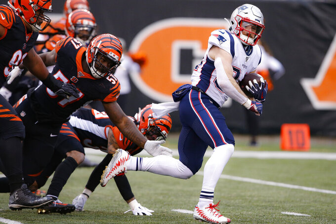 New England Patriots running back Rex Burkhead (34) breaks away from Cincinnati Bengals linebacker Germaine Pratt (57) and runs in for a touchdown in the second half of an NFL football game, Sunday, Dec. 15, 2019, in Cincinnati. (AP Photo/Gary Landers)