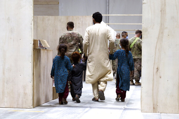 In this image provided by the U.S. Army, Afghan evacuees walk toward a medical screening station while in-processing at Camp Buehring, Kuwait, on Monday, Aug. 23, 2021. (1st Lt. James Mason/U.S. Army via AP)