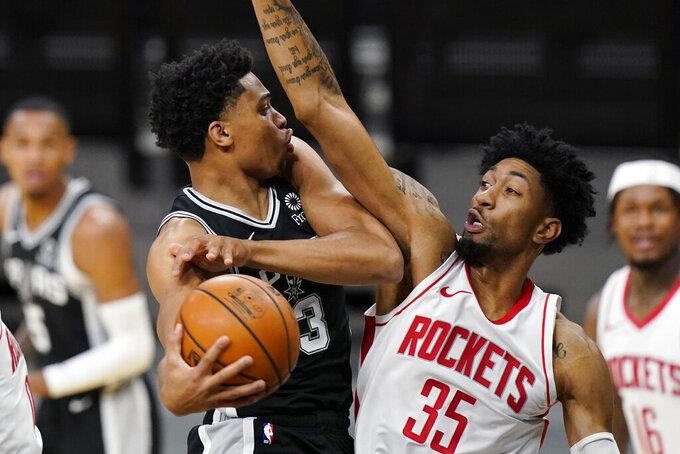 San Antonio Spurs forward Keldon Johnson (3) drives to the basket against Houston Rockets center Christian Wood (35) during the first half of an NBA basketball game in San Antonio, Thursday, Jan. 14, 2021. (AP Photo/Eric Gay)
