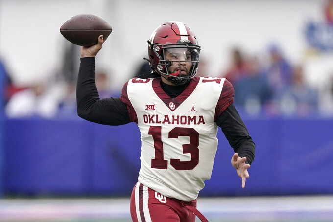 Oklahoma quarterback Caleb Williams passes the ball during the first half of an NCAA college football game against Kansas Saturday, Oct. 23, 2021, in Lawrence, Kan. (AP Photo/Charlie Riedel)