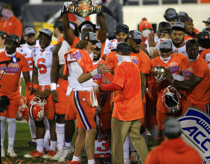 Clemson head coach Dabo Swinney celebrates with quarterback Trevor Lawrence (16) following their 34-10 victory over Notre Dame in the Atlantic Coast Conference championship NCAA college football game, Saturday, Dec. 19, 2020, in Charlotte, N.C. (AP Photo/Brian Blanco)