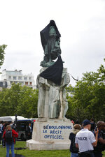 French military commander Joseph Gallieni statue is covered with a black cloth and with a graffiti reading « Down with the official version » during an action held by anticolonial activists, in Paris, Thursday, June 18, 2020. Gallieni began a colonial career at the end of the 19th century and later played an important role during First World War as a military governor of Paris. Gallieni used brutal methods to quell rebellion of local populations in French colonies, including as a governor of Madagascar where he abolished the 350-year-old monarchy on the island. (AP Photo/Thibault Camus)