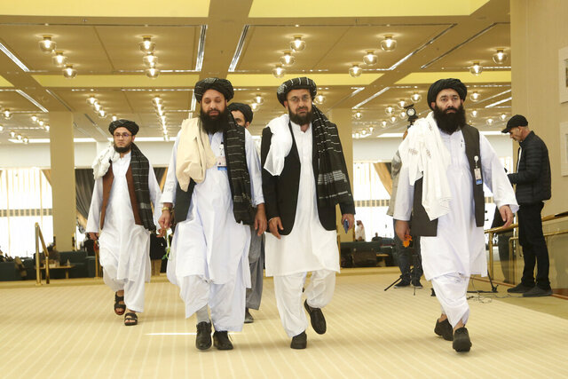 FILE- In this Feb. 29, 2020, file, photo, Afghanistan's Taliban delegation arrive for the agreement signing between Taliban and U.S. officials in Doha, Qatar. Taliban officials said Friday, July 17, 2020 that the son of the movement's feared founder has been put in charge of its military wing and added powerful figures to its negotiating team ahead of expected talks aimed at ending Afghanistan's decades of war, The moves mark one of the most significant shake-ups in years. (AP Photo/Hussein Sayed, File)