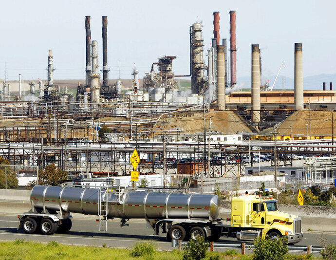 FILE - In this March 9, 2010, file photo a tanker truck passes the Chevron oil refinery in Richmond, Calif. A federal appeals court ruled Tuesday, May 26 against major oil companies in lawsuits brought by California cities and counties seeking damages for the impact of climate change. A panel of the 9th U.S. Circuit Court of Appeals said state courts are the proper forum for the lawsuits alleging that Big Oil promoted petroleum as environmentally responsible when producers knew it was causing damage. (AP Photo/Paul Sakuma, File)