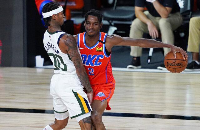 Oklahoma City Thunder's Shai Gilgeous-Alexander (2) drives into Utah Jazz's Jordan Clarkson (00) during the second half of an NBA basketball game Saturday, Aug. 1, 2020, in Lake Buena Vista, Fla. (AP Photo/Ashley Landis, Pool)