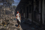 A pregnant woman looks on as she stands among debris at the fire damaged refugee and migrant camp of Moria on Lesbos island, Greece Wednesday, Sept. 9, 2020. Officials said the original fire was started by camp residents angered by the lockdown measures and isolation orders imposed after 35 people tested positive for COVID-19. (AP Photo/Petros Giannakouris)