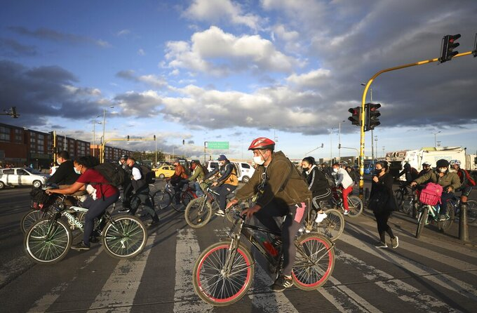 Commuters ride their bicycles, most of them to their jobs, in Bogota, Colombia, Friday, Aug. 28, 2020. The city has mandated that public parking lots expand spaces for bicycles by 20% and refurbished paths that run along busy roads next to cars. (AP Photo/Fernando Vergara)