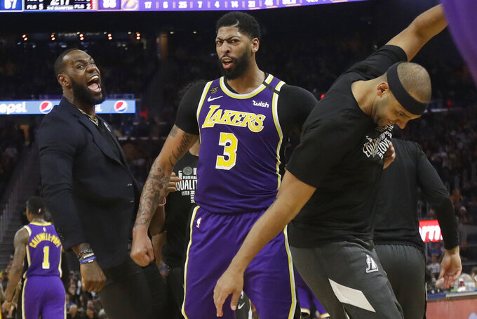 Los Angeles Lakers' LeBron James, left, celebrates with Anthony Davis (3) and Jared Dudley during the second half of an NBA basketball game against the Golden State Warriors in San Francisco, Thursday, Feb. 27, 2020. (AP Photo/Jeff Chiu)
