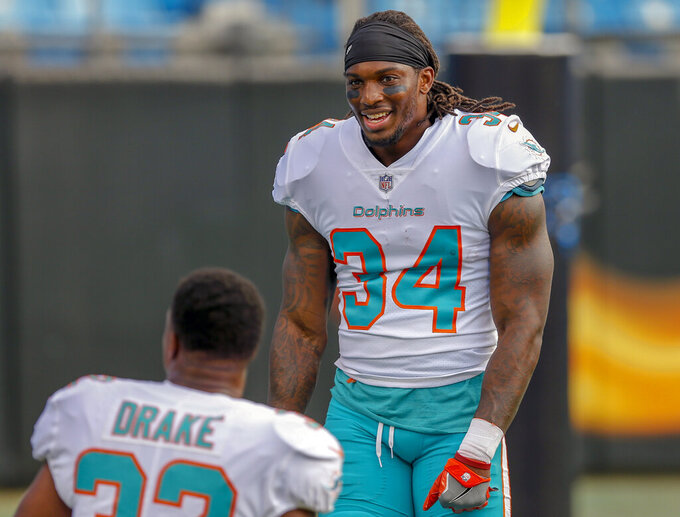 FILE - In this Aug. 17, 2018, file photo, Miami Dolphins running back Senorise Perry, right, talks with teammate Kenyan Drake before a preseason NFL football game against the Carolina Panthers, in Charlotte, N.C. The Buffalo Bills continue stockpiling free agents by signing running back and return specialist Senorise Perry to a one-year contract. The 27-year-old Perry has three seasons of NFL experience, including the past two with the Dolphins. (AP Photo/Nell Redmond, File)