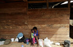 In this May 10, 2019 photo, a migrant woman and her son rest under a wooden house in Peñitas, Darien Province, Panama. According to the National Border Service of Panama, 7,316 migrants have come through the Darien Gap so far this year. (AP Photo/Arnulfo Franco)