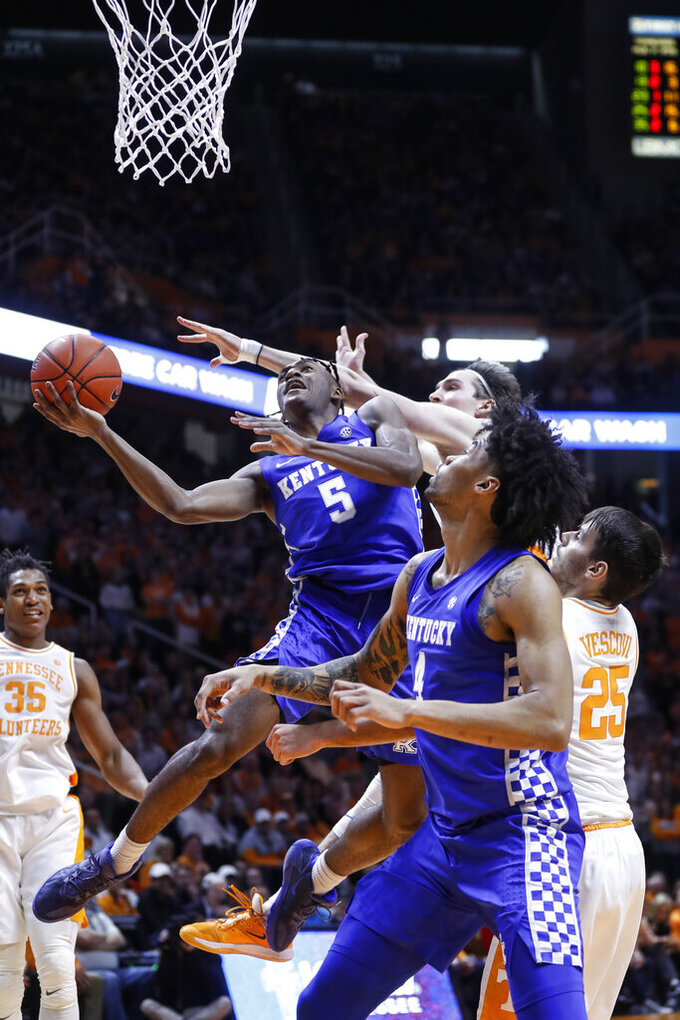 FILE - In this Feb. 8, 2020, file photo, Kentucky guard Immanuel Quickley (5) goes to the basket past Tennessee forward John Fulkerson, obscured at rear center, during an NCAA college basketball game in Knoxville, Tenn. Quickley was selected to the Associated Press All-SEC first team announced Tuesday, March 10, 2020. (AP Photo/Wade Payne, File)