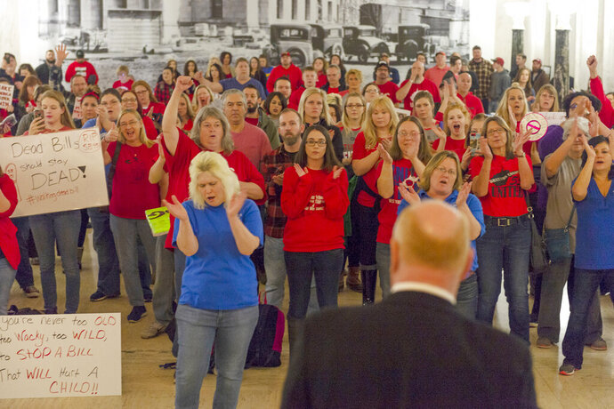 FILE - In a February 20, 2019 file photo, teachers and school personnel clap as West Virginia Education Association President Dale Lee speaks in front of the House of Delegates chamber at the West Virginia State Capitol in Charleston, W.Va. on the second day of a statewide strike by teachers and school personnel. A sweeping West Virginia GOP education bill that allows the creation of charter schools violates the state Constitution, according to The West Virginia Education Association, that plans to sue over the legislation. The West Virginia Education Association released a statement Wednesday, July 10, 2019 saying it has sent a formal letter notifying the attorney general of their intention to sue. (Craig Hudson/Charleston Gazette-Mail via AP, File)